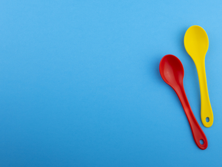 Yellow red plastic spoons on blue background with copyspace for text