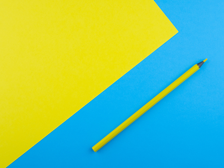 Wooden pencils on yellow and blue background with copyspace for text Banco de Imagens
