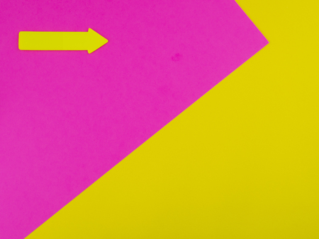 Yellow and pink background with yellow arrow and copyspace for text Banco de Imagens