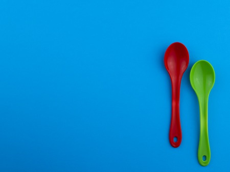 Red green plastic spoons on blue background with copyspace for text