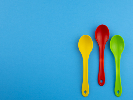 Yellow red green plastic spoons on blue background with copyspace for text 免版税图像