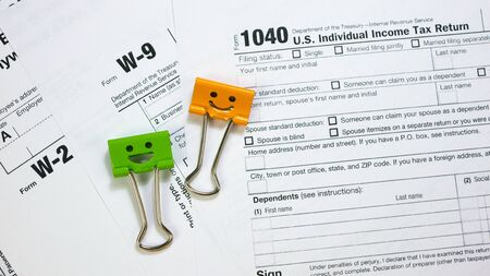 IRS 1040, W-9 and W-2 U.S. Tax Form with Green and Orange Color Binder Clips. Wage and tax statement concept