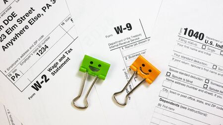 Green and Orange Color Binder Clips on W-9, W-2 and 1040 Tax Form. Tax Payment Concept. Filing Taxes Document on Table in Office. Individual Income Tax Return Zdjęcie Seryjne