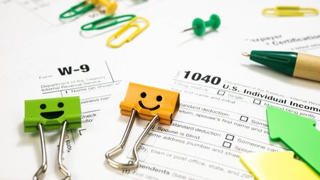 Green Pen on 1040 Tax Form and W-9. Smile Orange and Green Binder Clips. Individual Income Tax Return. Filing Taxes Document on Table in Office Concept. Have time to pay taxes by April