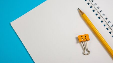 Blank paper notepad with yellow and blue binder clips on blue background. Spiral notebook and smile binder clips on table. Office supplies or education concept