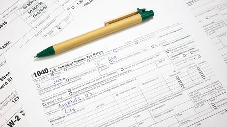 Filled 1040 Tax Form with pen. IRS W-9 U.S. document and Green Pen. Wage and tax statement concept Imagens