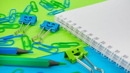 Office Paper Clip, Smile Binder Clips and Pencils on Notepad. Office supplies on Green and Blue Background. Open spiral notebook on table. Knowledge or education concept. Back to school 版權商用圖片