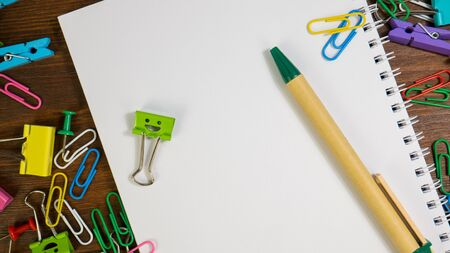 Smiles Binder Clips with School Office Supplies. Paper notebook with green pen. School stationery on brown wooden table. Concept of back to school, education or knowledge