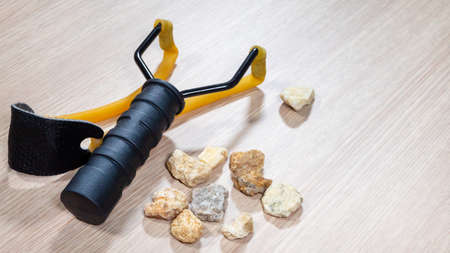 Man hand take stone with slingshot small hand-powered projectile weapon on wooden background. Classic form Y-shaped frame held in off hand with two rubber strips. Pocket that holds projectile