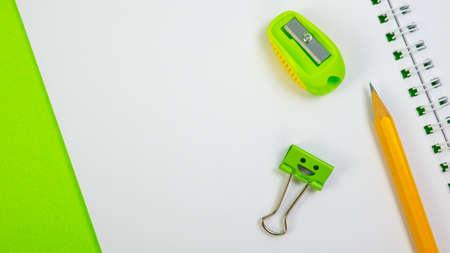 Yellow Pencil and Green Pencil Sharpener with Smile Binder Clip on School Notepad on Green Background. Spiral notebook on table. Office supplies or school education concept