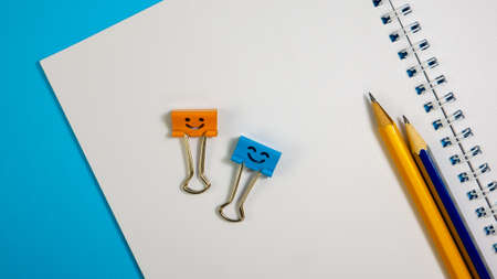 Orange and Blue Smile Binder Clips with Pencils on Notepad. Office supplies on Blue Background. Open spiral notebook on table. Education or knowledge concept. Back to school