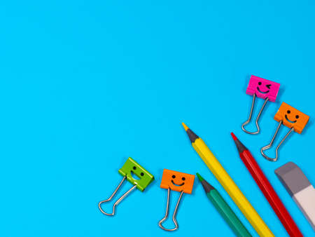 Orange, Green and Pink Smile Binder Clips with Pencils on Blue Background. Funny office supplies and rubber on table. Education or knowledge concept. Back to school