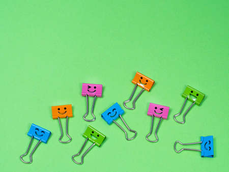 Multicolored different funny smile metal binder clip or multicolored paperclip on green background with copyspace for text Archivio Fotografico