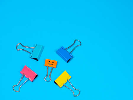 Bullying and depression concept. Funny multicolored smile metal binder clip on blue background with copyspace for text. Use of force, coercion, threat, to abuse, aggressively dominate or intimidate