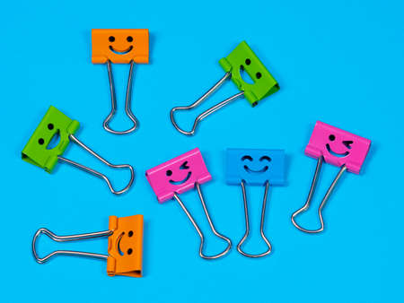 Funny smile yellow red green metal binder clip or multicolored paperclip on blue background with copyspace for text Archivio Fotografico