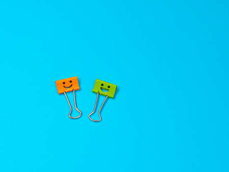 Funny smile yellow orange green metal binder clip or multicolored paperclip on blue background with copyspace for text Archivio Fotografico