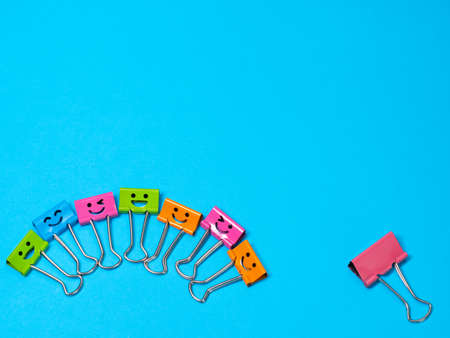 Fear, stress, emotion concept. Funny smile metal binder clip. Multicolored paperclip on blue background with copyspace for text Archivio Fotografico