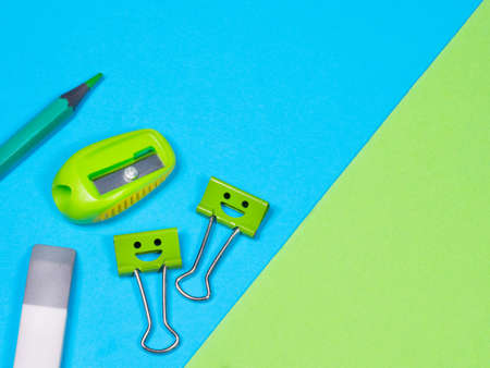 Green Pencil, Eraser, Smiles Binder Clips on Blue Background. Office supplies on table. Education concept. Back to school. Eraser or rubber