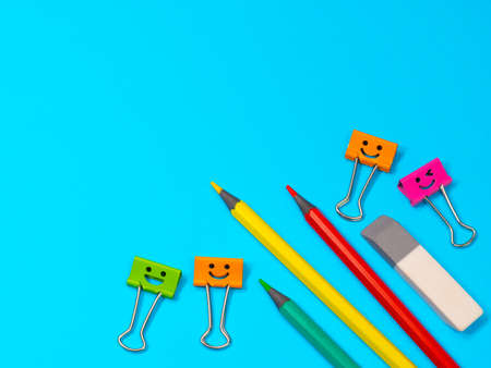 Smiles Binder Clips with Yellow, Green and Red Pencils on Blue Background. Office supplies on table. Education concept. Back to school. Eraser or rubber Archivio Fotografico