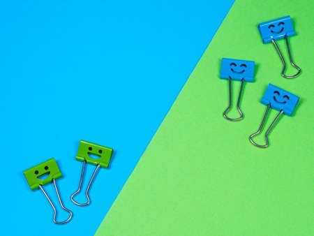 Funny smile blue green metal binder clip or multicolored paperclip on blue green background with copyspace for text Archivio Fotografico
