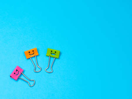 Orange, green and pink funny smile metal binder clip. Multicolored paperclip on blue background with copyspace for text