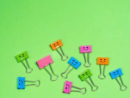 Funny smile metal binder clip or multicolored paperclip on green background with copyspace for text