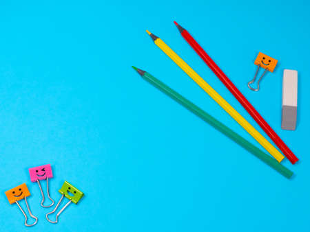 Smiles Binder Clips with Yellow, Green and Red Pencils on Blue Background. Office supplies on table. Education concept. Back to school