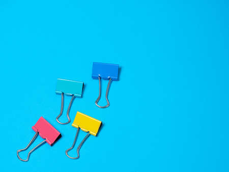 Multicolored different metal binder clip or multicolored paperclip. Blue background with copyspace for text