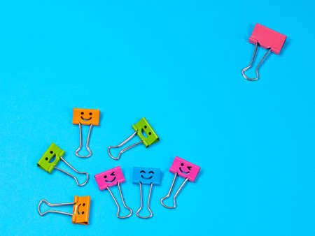 Bullying, loneliness and depression concept. Funny smile metal binder clip. Multicolored paperclip on blue background with copyspace for text