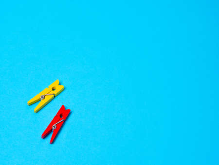 Yellow and red wood clothespins pegs on blue background and free space for text