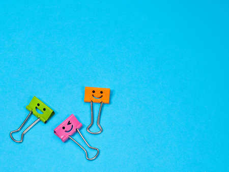 Orange, green and pink funny smile metal binder clip on blue background with copyspace for text