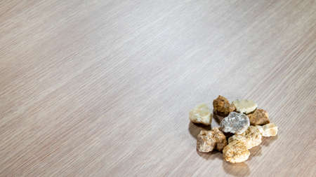 Different colored small stones on light brown table