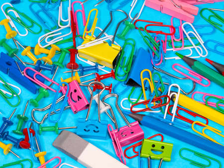 Paper clips on blue background. View from above with copy space School supplies on pink background. Pens, pencils, scissors, paper clips and a marker on the table. View from above with copy space Archivio Fotografico