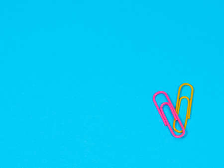 Colored paper clips on blue background with copyspace