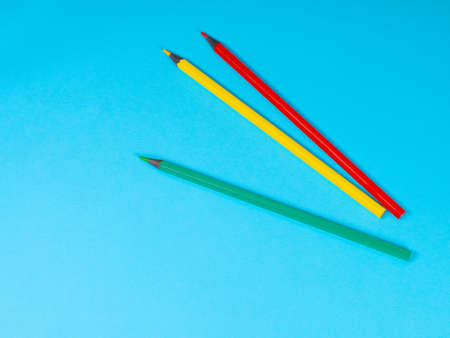 Red, Yellow and Green Colored Pencils on Blue Background. Office supplies, education concept. Back to school