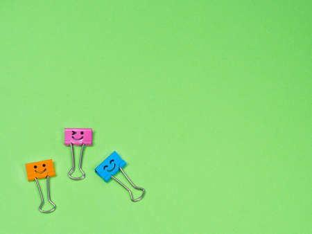 Orange, blue and pink smile funny metal binder clip or multicolored paperclip on green background with copyspace for text