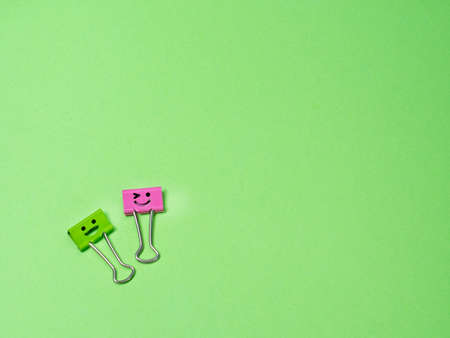 Green and pink funny smile metal binder clip or multicolored paperclip on green background with copyspace for text