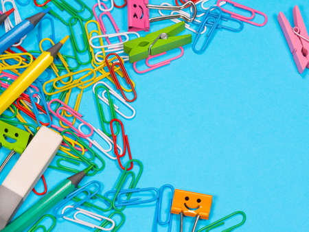 Paper clips on blue background with copyspace. School supplies. Pencils, paper clips, eraser, clothespin. Back to school Archivio Fotografico