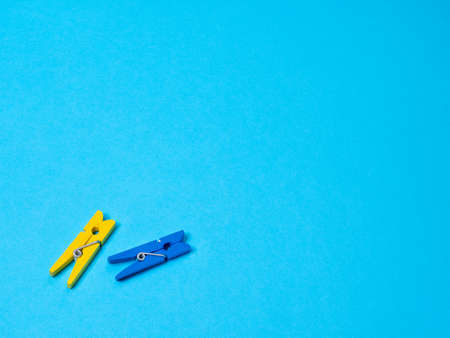 Blue and yellow wood clothespins pegs on a blue background and free space for text