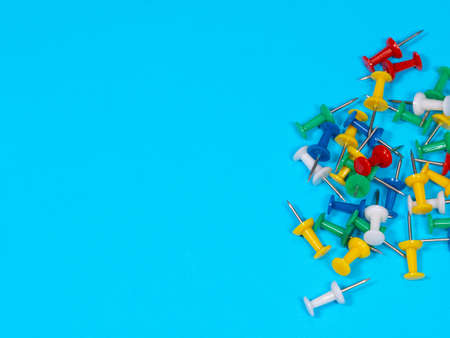 Color push pins on blue background for copyspace. Concept of office administrator business, financial inspector or secretary. Push-pin or map pin Archivio Fotografico