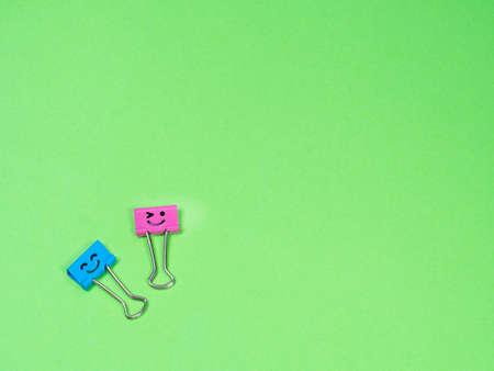 Funny blue and pink smile metal binder clip or multicolored paperclip on green background with copyspace for text Archivio Fotografico
