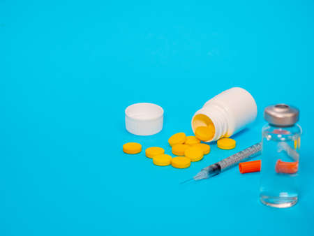 Syringe insulin with vial and yellow pills on blue background. Ready for vaccine injection. Pain treatment, illegal use, healthcare and medical concept vaccination