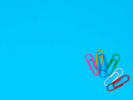 Collection of colorful paper clips on blue background with copyspace