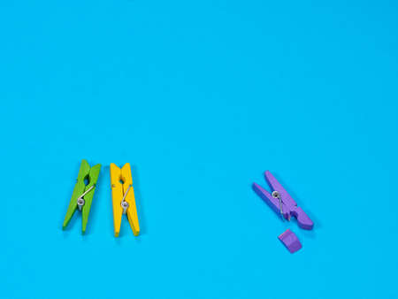 Violet wooden clothespin with fracture leg on blue background. Bullying, loneliness and depression concept. Copyspace for text Archivio Fotografico