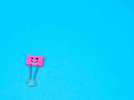 Pink funny smile metal binder clip. Multicolored paperclip on blue background with copyspace for text