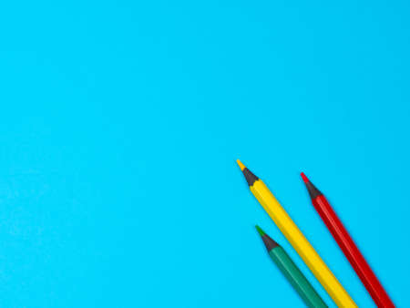 Green, Yellow and Red Pencils on Blue Background. Office supplies on table. Education concept. Back to school. Minimalism and abstract Archivio Fotografico