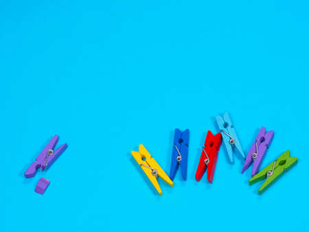 Wooden violet clothespin with fracture leg on blue background. Bullying, loneliness and depression concept. Copyspace for text Archivio Fotografico