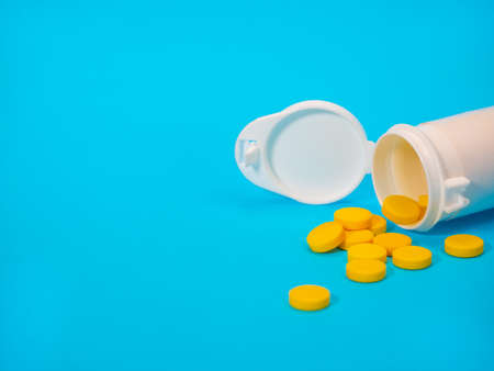 Yellow pills and plastic white bottle. Blue background with copy space for text. Healthy and medicine. Pain management. Drug abuse in teenage concept Archivio Fotografico