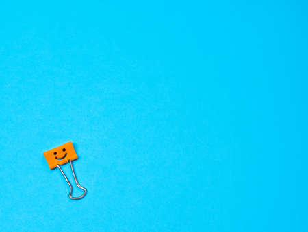 Funny smile metal binder clip or multicolored paperclip on blue background with copyspace for text Archivio Fotografico