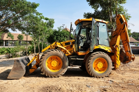A loader is commonly used to move a stockpiled material from ground level and deposit it into an awaiting dump truck or into an open trench excavation. photo